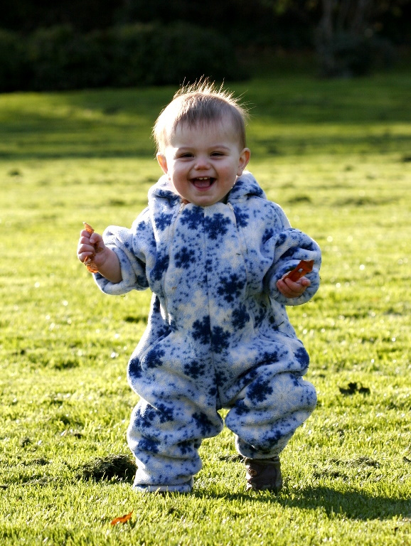 A smiling baby standing in a field