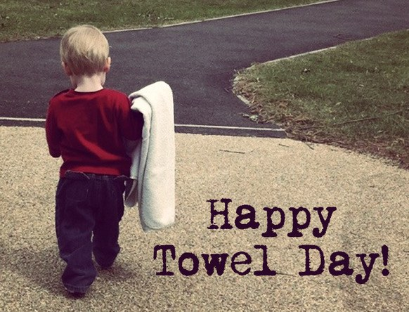 Toddler carrying blanket with caption Happy Towel Day!